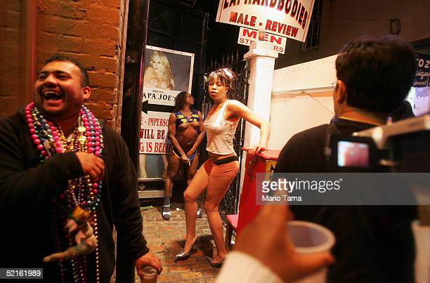 Female impersonators attempt to lure customers into a club on Bourbon Street after midnight following the official conclusion of Mardi Gras...