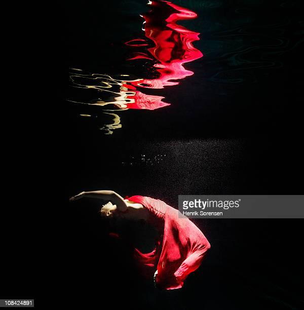 female in a red evening dress under water - vestito rosso foto e immagini stock