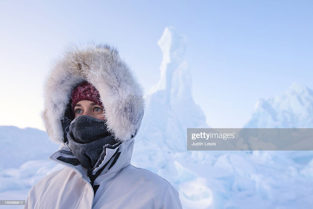 Female in arctic hood & jacket with icebergs : Stock Photo
