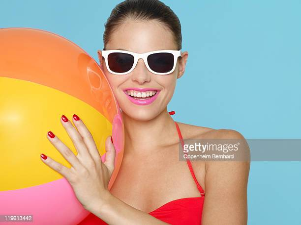 female in bikini holding beach ball