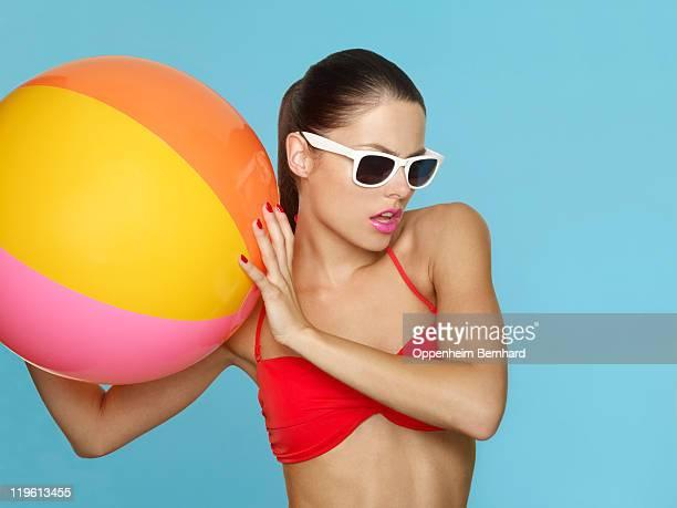 female in bikini holding beach ball