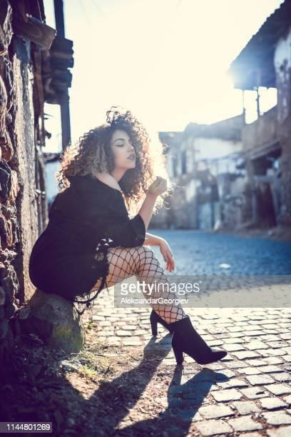 female in netted thigh highs sitting in old sunny street - medieval shoes stock pictures, royalty-free photos & images