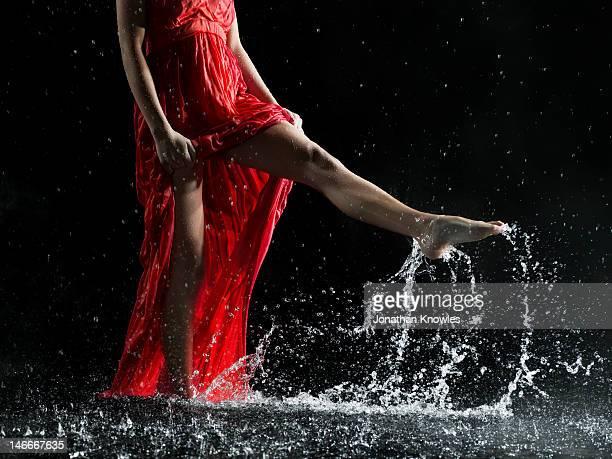 Female in red, legs splashing in water, cropped