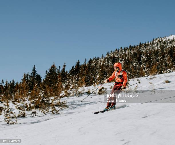 female in red skis down baldface mountain, nh on a cold morning. - ski holiday stock pictures, royalty-free photos & images