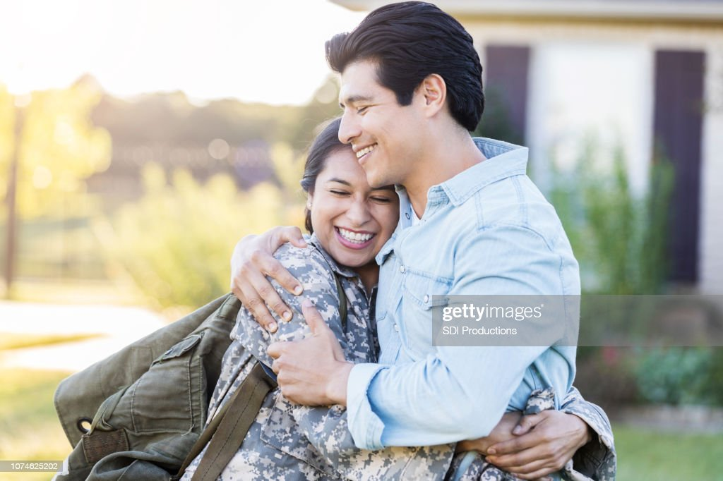Female in uniform shares a hug with her husband : Foto stock