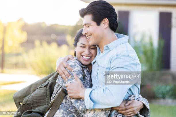 female in uniform shares a hug with her husband - esposa imagens e fotografias de stock