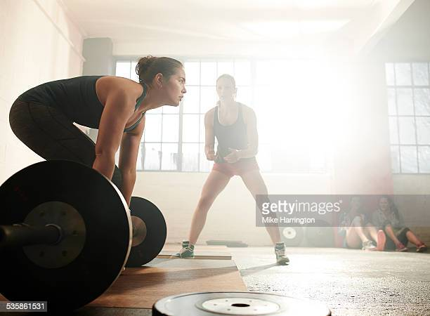 Female in warehouse gym, preparing for deadlift
