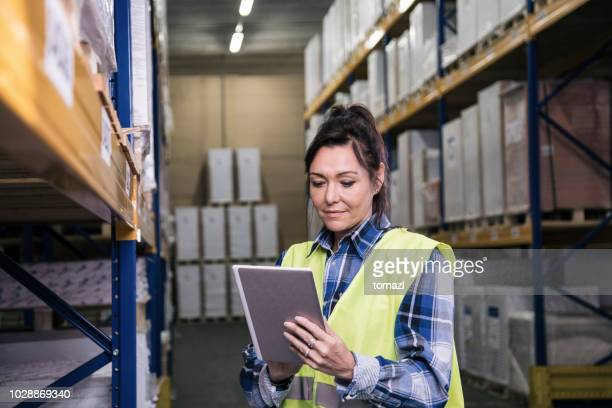 Female in warehouse on her digital tablet