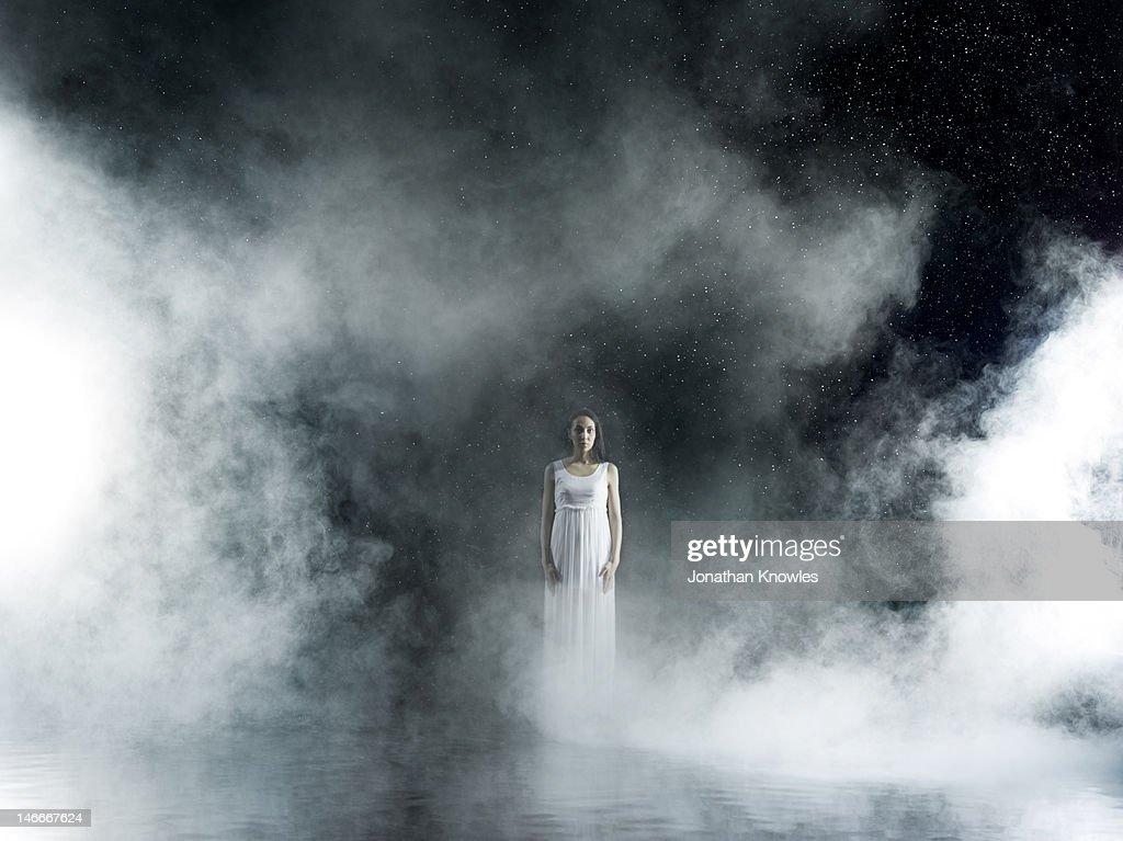 Female in white in rain,  misty night : Stock-Foto