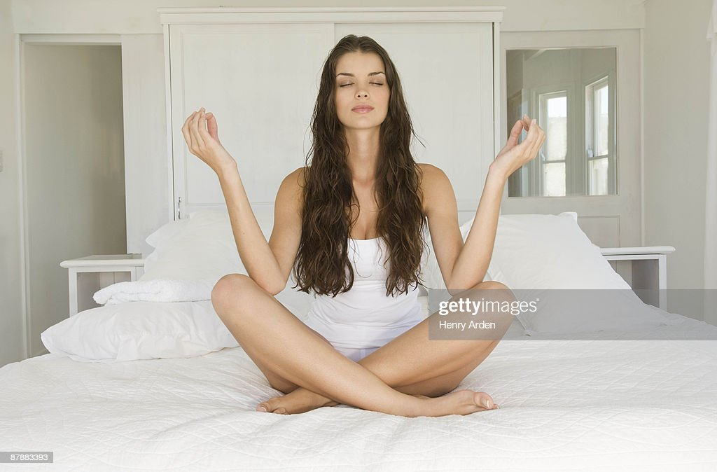 Female in yoga pose sitting on bed : Stock Photo