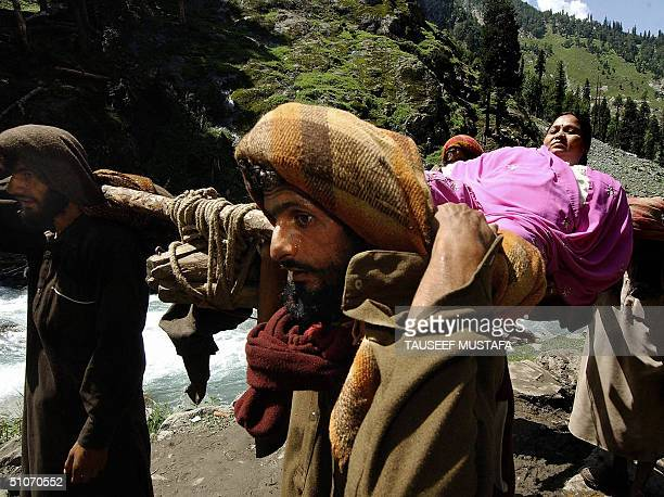 Female Indian Hindu pilgrim is carried by Muslim porters on a special bed in the village of Chandanwari some 114kms south of Srinagar.15 July 2004....