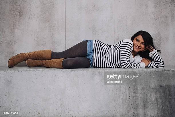 female indian laying on concrete wall - 横向きに寝る ストックフォトと画像