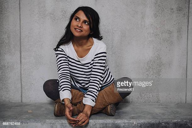 Female Indian sitting on concrete wall
