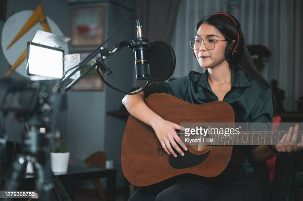female influencer playing acoustic guitar recording live stream - performance stock pictures, royalty-free photos & images
