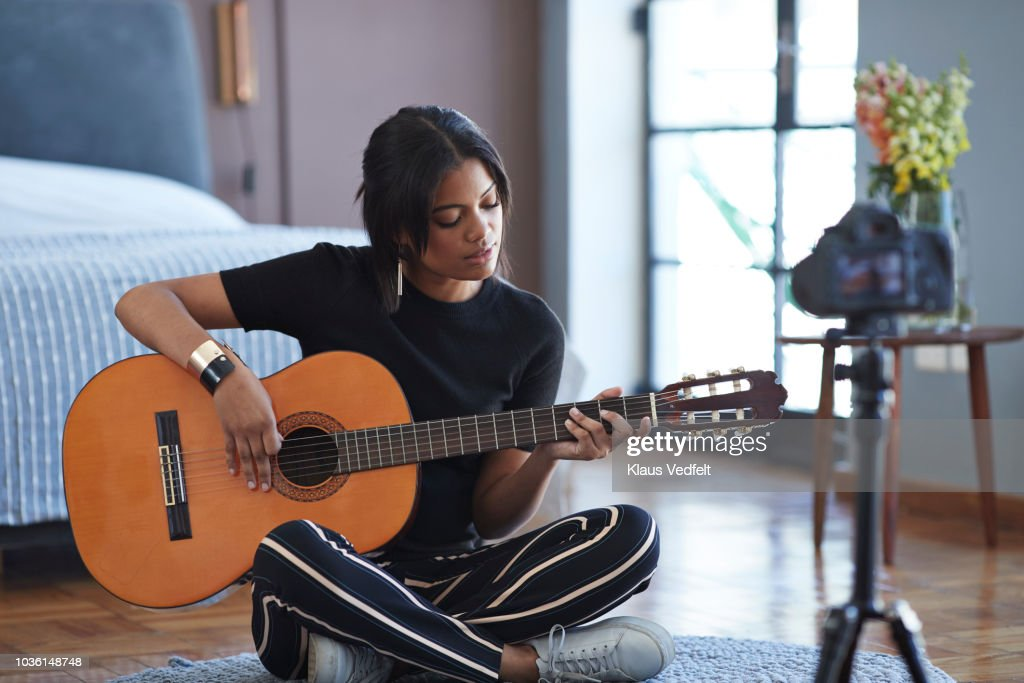 Female influencer recording for video blog with guitar lesson : Foto stock