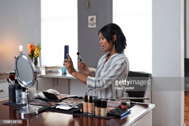 female influencer recording make-up tip videos using smartphone, for her blog - video call stock-fotos und bilder