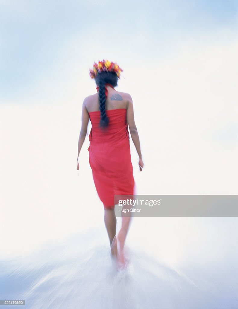 A female inhabitant with flowers in her hair walking through the water : Stock-Foto