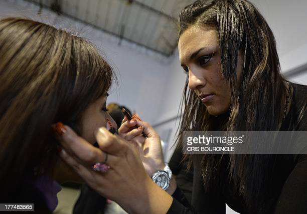 Female inmates put makeup on each other before a model show at the Piedras Gordas Model Penitentiary 11 km north of Lima on August 22 2013 Women most...