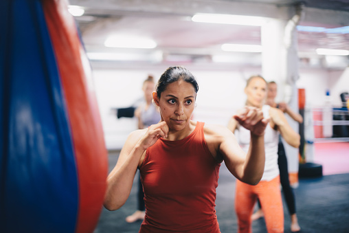 Female instructor and athletes standing in fighting stance while practicing martial arts at gym - gettyimageskorea