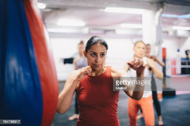 female instructor and athletes standing in fighting stance while practicing martial arts at gym - mid adult women stock pictures, royalty-free photos & images