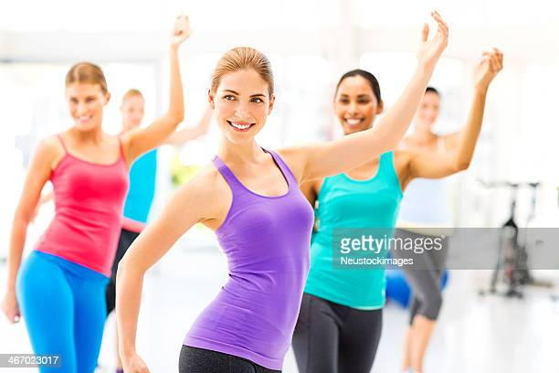 Female Instructor And Class Practicing Aerobic Dance In Gym