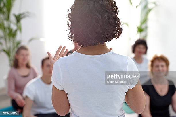 Female instructor guiding student during yoga class