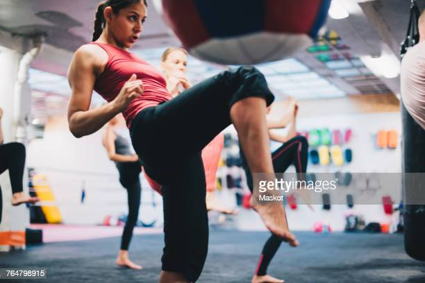 female instructor practicing kickboxing with athletes at gym - patadas fotografías e imágenes de stock