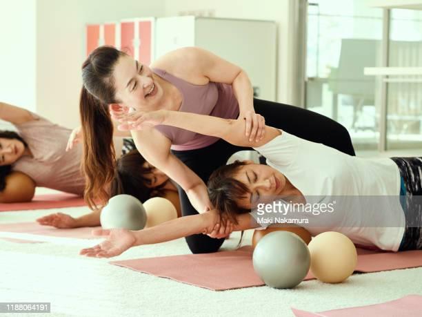 female instructor teaching matt pilates. - スポーツ施設 ストックフォトと画像