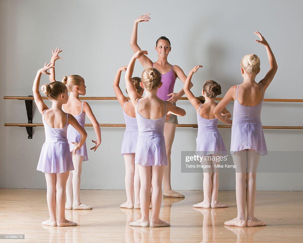 Female instructor training ballet dancers (6-7,8-9) in dance studio : Stock Photo