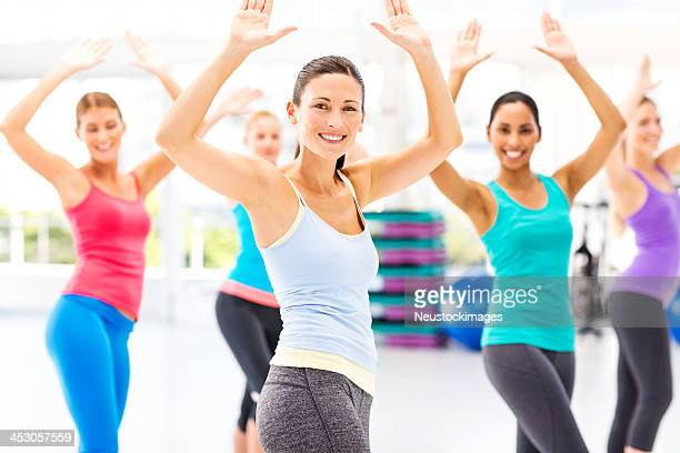 Female Instructor With Customers Practicing Aerobic Dance In Health Club