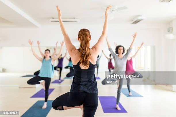 Instructeur féminin avec cours d'yoga dans le gymnase