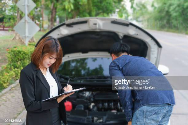 Female Insurance Agent Standing By Mechanic Repairing Car On Road