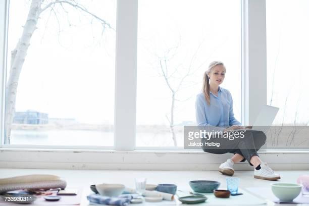 Female interior designer looking at ceramics and textiles on design studio floor
