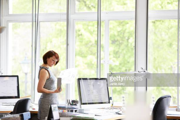 Female interior designer looking at swatch and blueprint in office