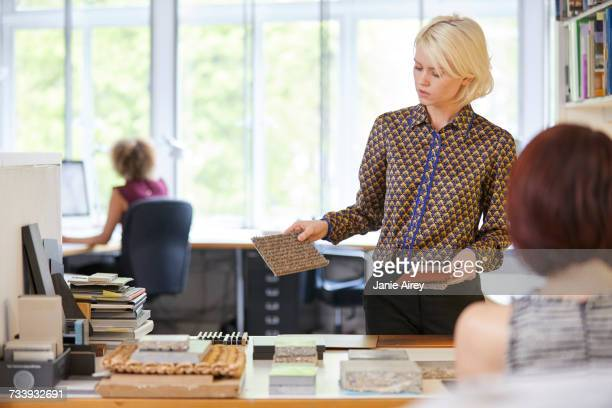 Female interior designer showing swatches to colleague in office