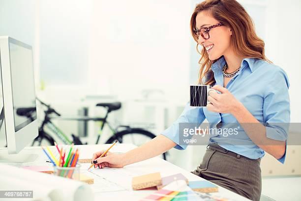 Hembra diseñador de interiores dibujar en el trabajo.