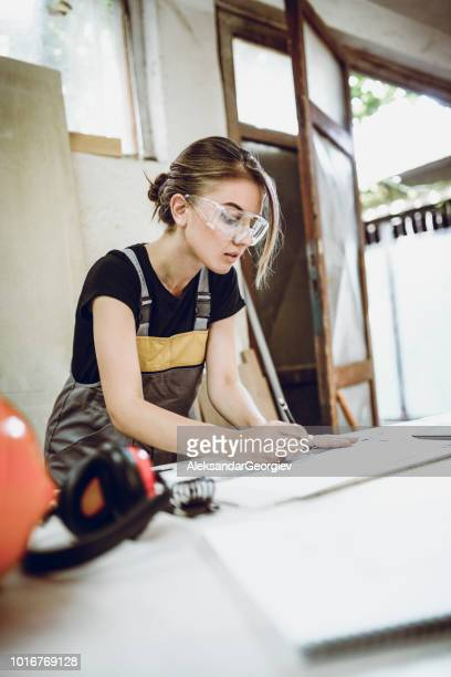 Female Interior Designer Writing Out Calculations In Notebook