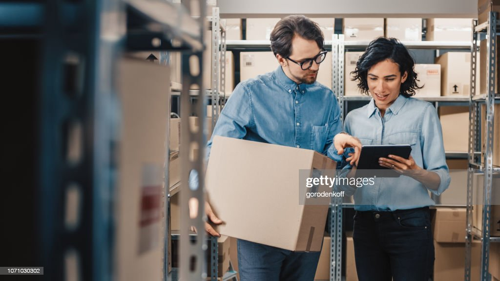 Female Inventory Manager Shows Digital Tablet Information to a Worker Holding Cardboard Box, They Talk and Do Work. In the Background Stock of Parcels with Products Ready for Shipment. : Stock Photo