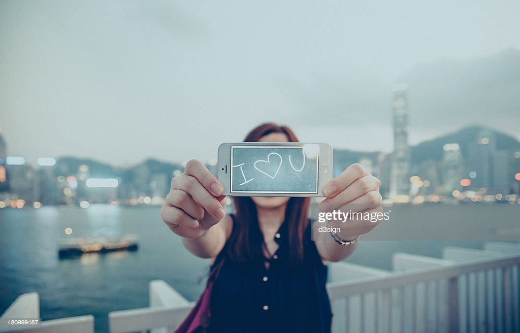 "Female is saying ""I Love You"" with her smartphone : Stock Photo"