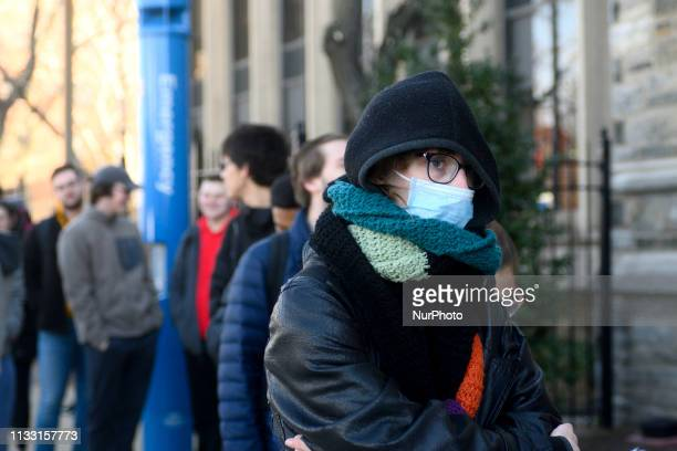 A female is seen wearing face mask as students faculty and staff line up outside an emergency clinic at Temple University in Philadelphia PA on March...