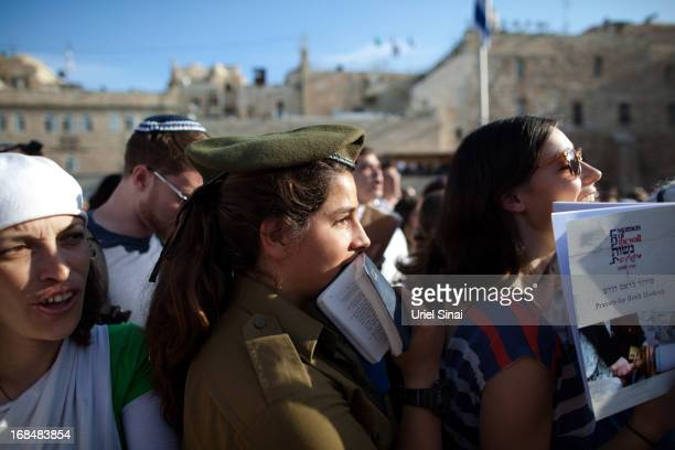 A female Israeli soldier joins members of the religious group 'Women Of The Wall' as they hold a prayer service to mark the first day of the Jewish...