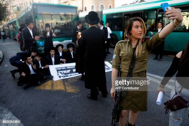TOPSHOT A female Israeli soldier uses her cell phone to take a selfie photograph with ultraOrthodox Jewish demonstrators in the background who are...