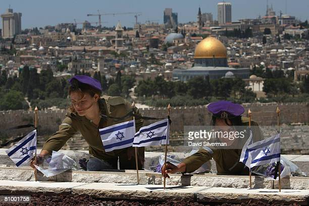 Female Israeli soldiers place flowers and flags on the graves of Jews killed in the battle for Jerusalem during Israel's 1948 War of Independence on...