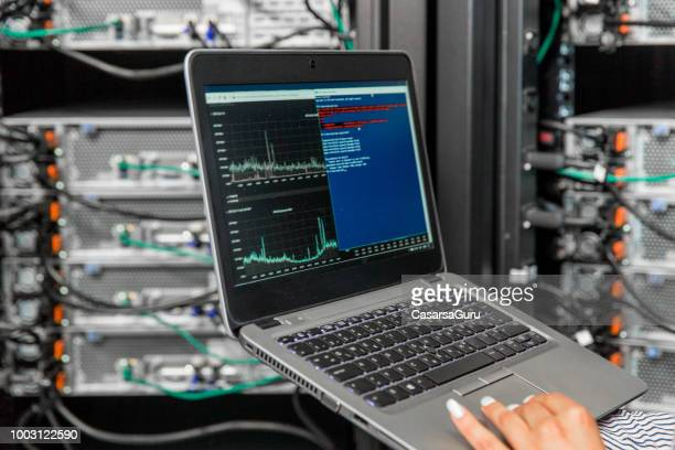 female it engineer using laptopf for analysis of network servers in server room - surveillance stock pictures, royalty-free photos & images
