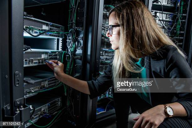 female it engineer working in server room - cable stock pictures, royalty-free photos & images