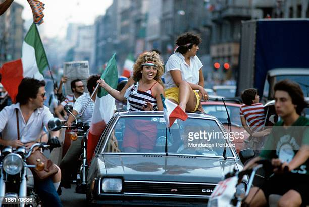 A female Italian soccer fan waves the Italian flag sticking out of a car's hood while around her the street is full of honking cars the Italy...