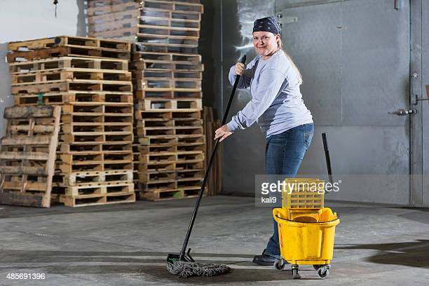 female janitor mopping floor in warehouse - janitorial services stock photos and pictures
