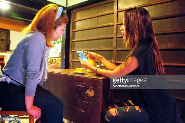 Female Japanese customer showing images to owner for inspiration