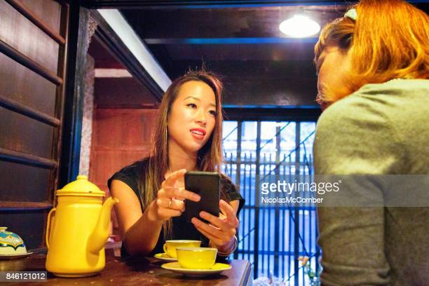 female japanese customer showing images to owner for inspiration - hot women pics stock pictures, royalty-free photos & images