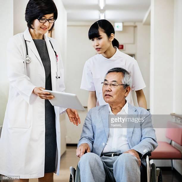 Female japanese doctor showing Data on Digital Tablet